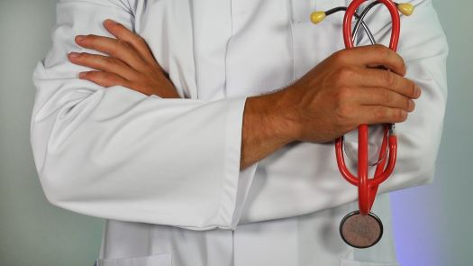a doctor wearing a white lab coat holding a red stethoscope depicting nomad health