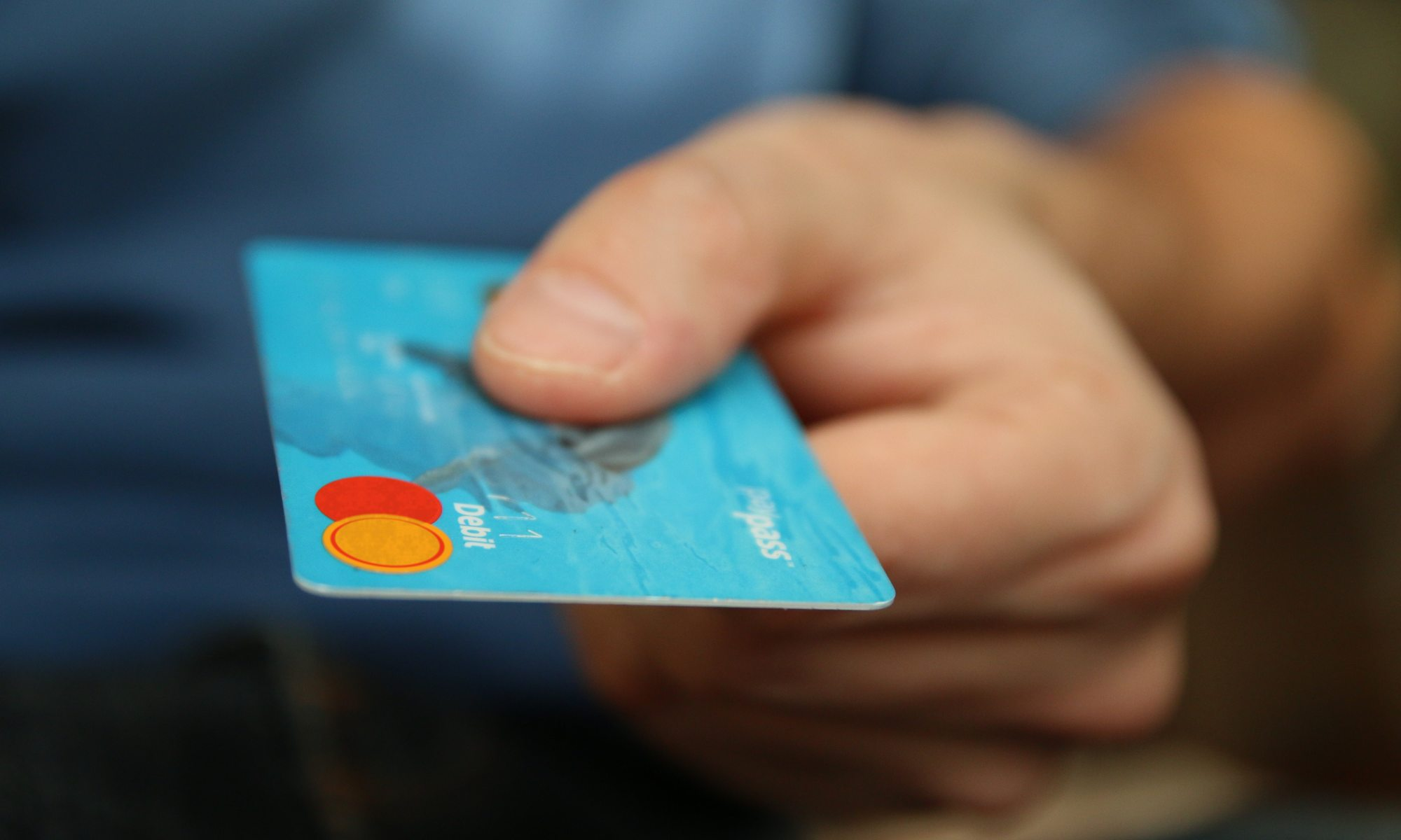 picture showing a hand holding out a debit card