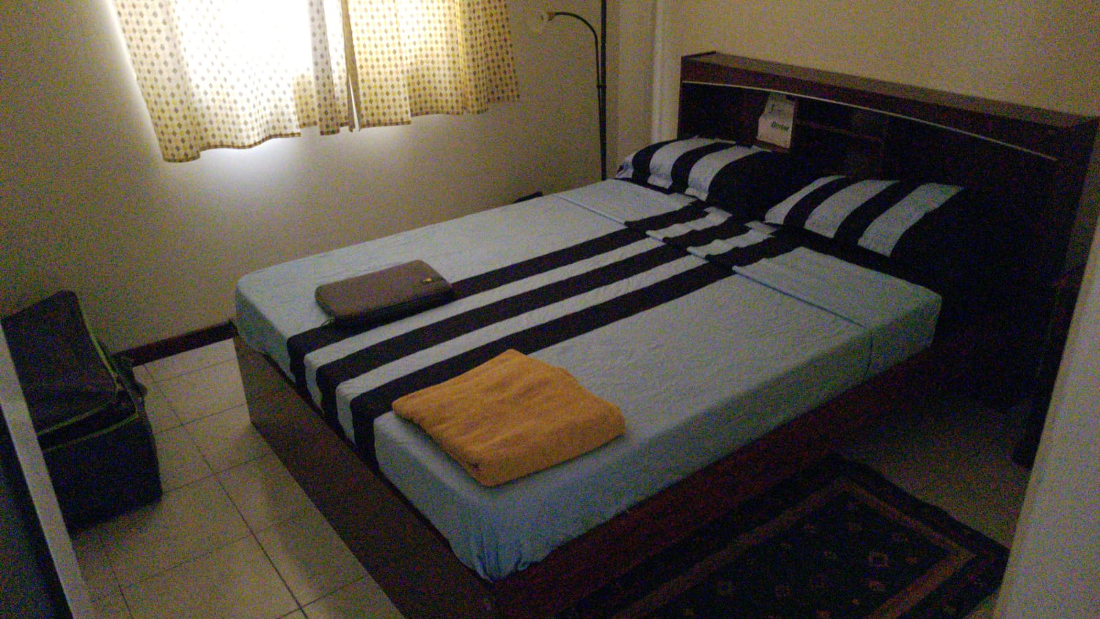a bedroom with a bed with blue bedsheets