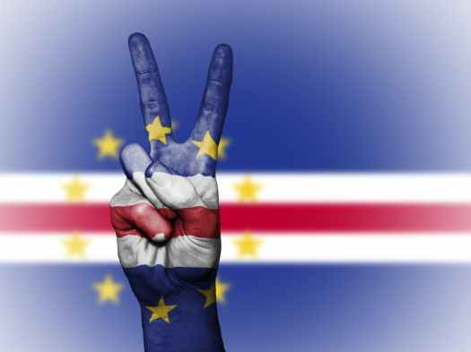 picture showing the flag of cabo verde with a finger making the peace sign