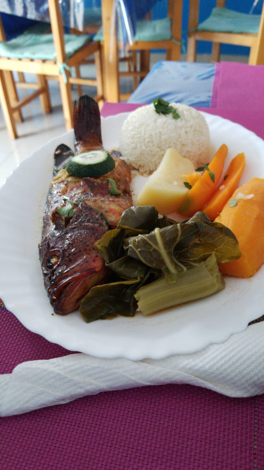 a dish with fish. vegetables and rice
