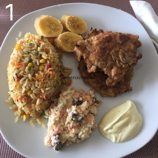 a plate of fried rice with some boiled plantain and fired chicken, some mayonnaise and