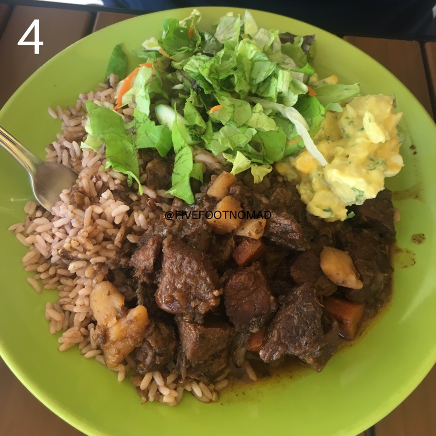 a plate showing rice with lentils with beef stew, potato and lettuce salad