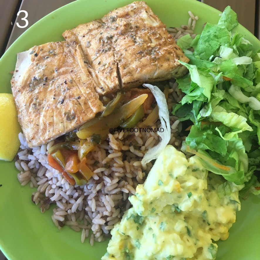 a plate of fish with rice and lentils with potato salad and lettuce salad on the side