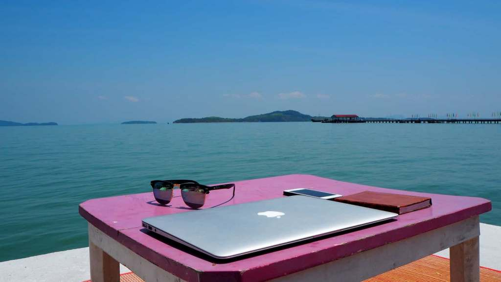 laptop, phone, notebook on  table by the sea