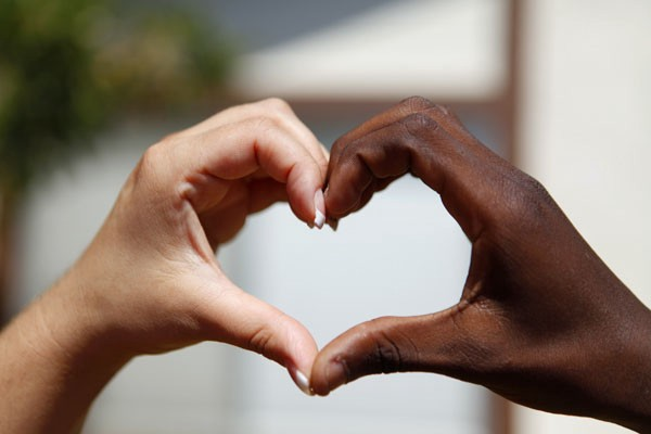 white hand and black hand forming love shape