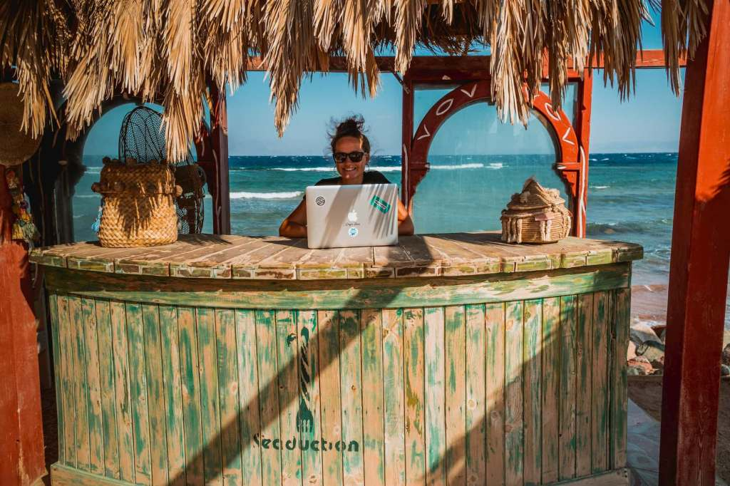 lady working on her laptop by the beach