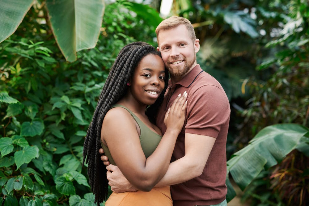 white man holding black woman