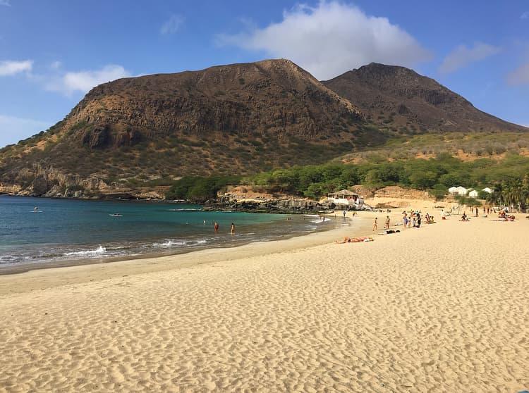 white sand beach with mountain background