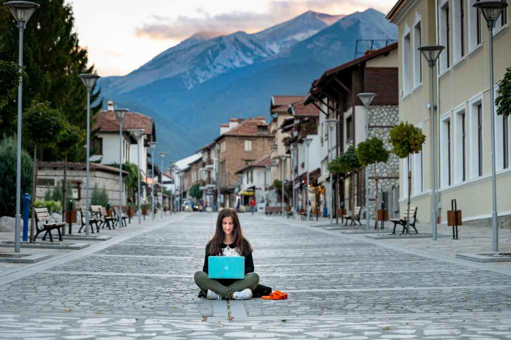 lady working on her laptop sitting in the middle of the street